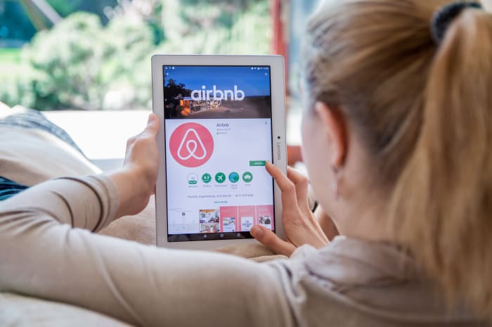 אישה גולשת באתר Airbnb באמצעות טאבלט (ShutterStock)