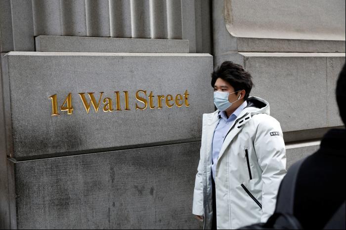 אדם עם מסכה על פניו עובר ליד וול סטריט שבניו יורק ב-6 במרץ 2020 (רויטרס)