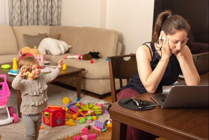 אמא מתוסכלת לפעוטה מנסה לעבוד מהבית. ShutterStock